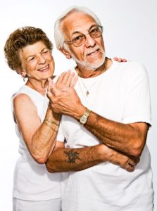 senior man and woman, dressed in white, holding hands.